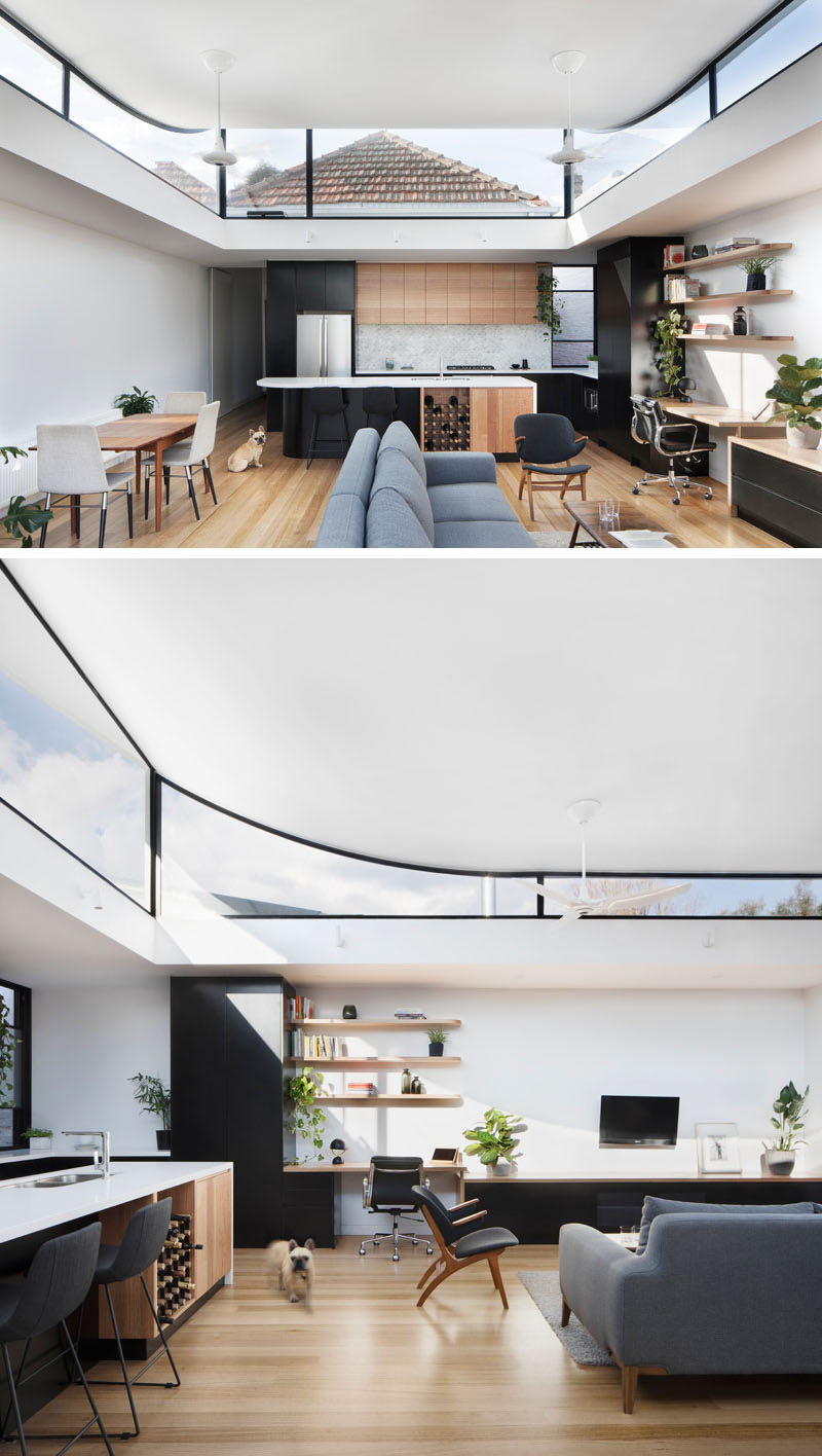 This modern house extension has an open plan room with a living area, dining space, home office and kitchen. Around the top of the extension, a perimeter of clerestory windows raises the roof and curves up at the end closest to the original house, with the other end cantilevering over the back deck. The curve of the ceiling draws the eye upwards to make the space appear larger than it is.