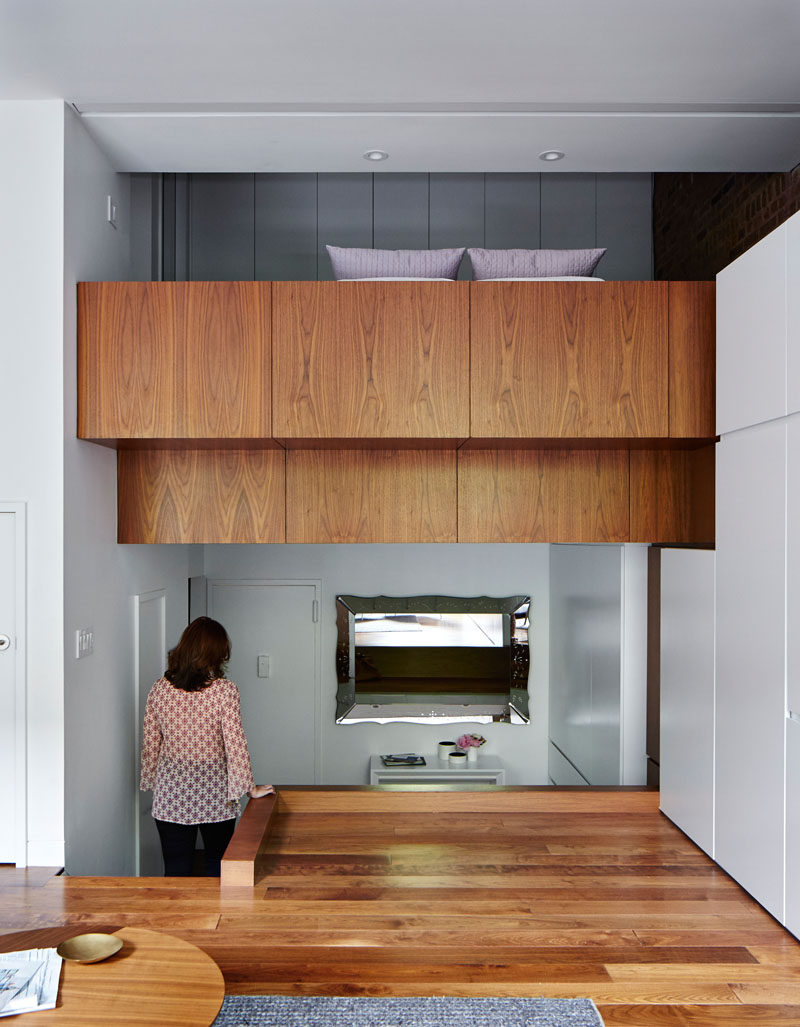 To enlarge the lofted bedroom in this apartment, the sleeping loft was extended out into the living room and covered in walnut paneling, tying in with the flooring.