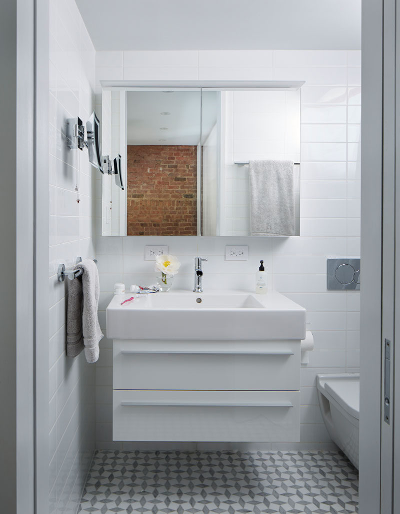 This small bathroom features floor-to-ceiling white tiles, while the mirror reflects the brick on the wall in the bedroom.