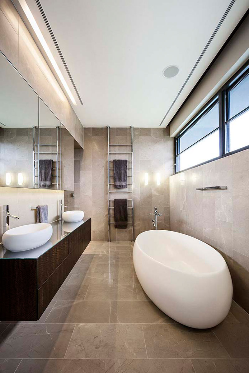 In this modern light grey tiled bathroom, a large rectangular mirror reflects light from the hidden lighting in the ceiling, and from the windows above the freestanding white bathtub.