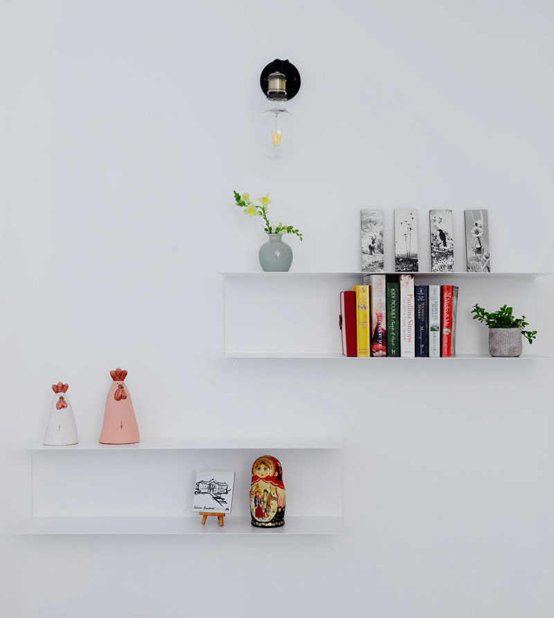 In this modern apartment, a set of minimalist white floating shelves are mounted below a single bulb, black wall sconce. The ornaments and books displayed add a pop of color to the white wall.