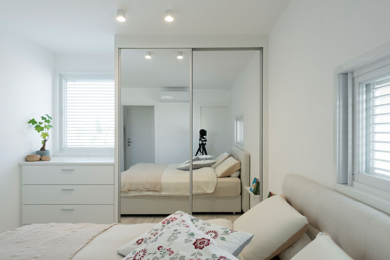 In this modern master bedroom, the decor is almost entirely white making it nice and bright. Placed beside a white built-in dresser is a closet with a sliding mirrored door that helps to reflect the light.