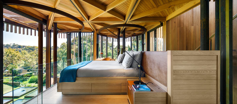Upstairs in this modern tree house bedroom, a glass safety railing has been added in front of the bed to provide an unobstructed view of the trees.