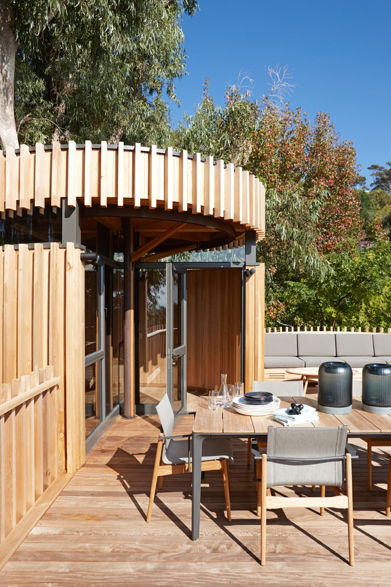 This modern grown-up tree house has a rooftop deck with a dining table and built-in seating. Being on the roof of the home makes it feel like you are dining in, and with the tops of the trees.