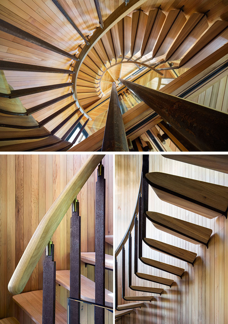 This spiral staircase with a wood handrail and steps wraps around steel support beams, and leads to the upper levels of the grown-up tree house.
