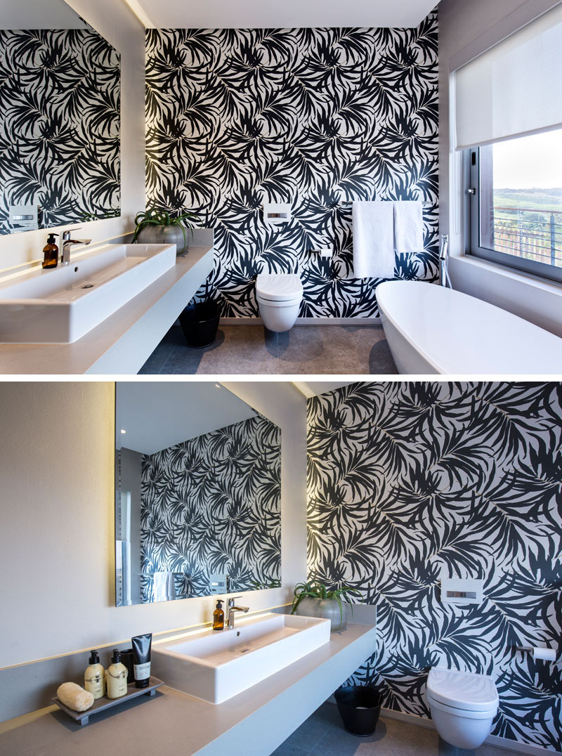 The black and white wallpaper on the accent wall of this modern bathroom is bold, making the white bath, toilet, vanity and decor standout. A large window with a white pull down privacy blind, provides views of outside when wanted.