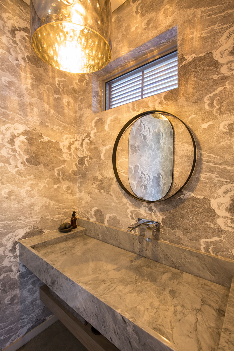 The grey and white cloud wallpaper compliments the large marbled stone inlaid sink, and textured pendant light in this modern bathroom.