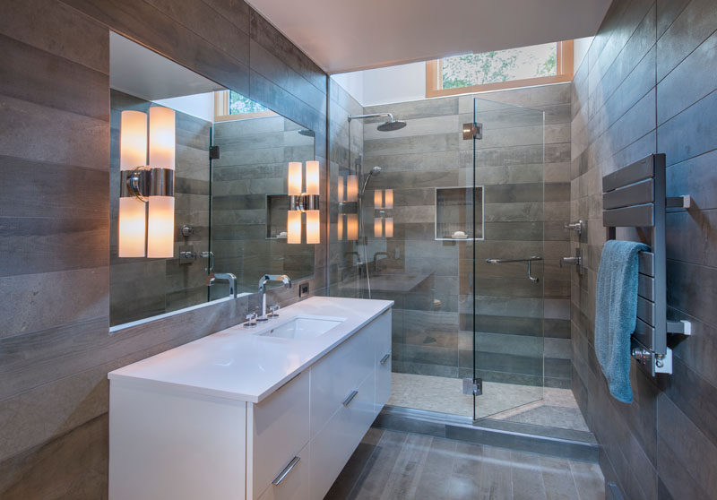 In this modern bathroom, grey tiles adorn the walls, while a glass shower surround allows the light from the window to travel through to the vanity.
