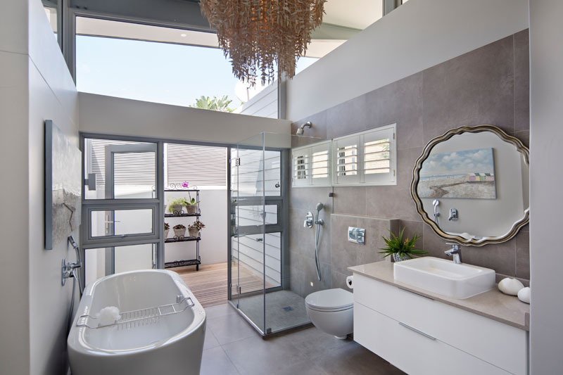 In this modern bathroom, there's a freestanding bathtub, a glass enclosed shower, a large textured chandelier and a private patio that's home to an outdoor shower.