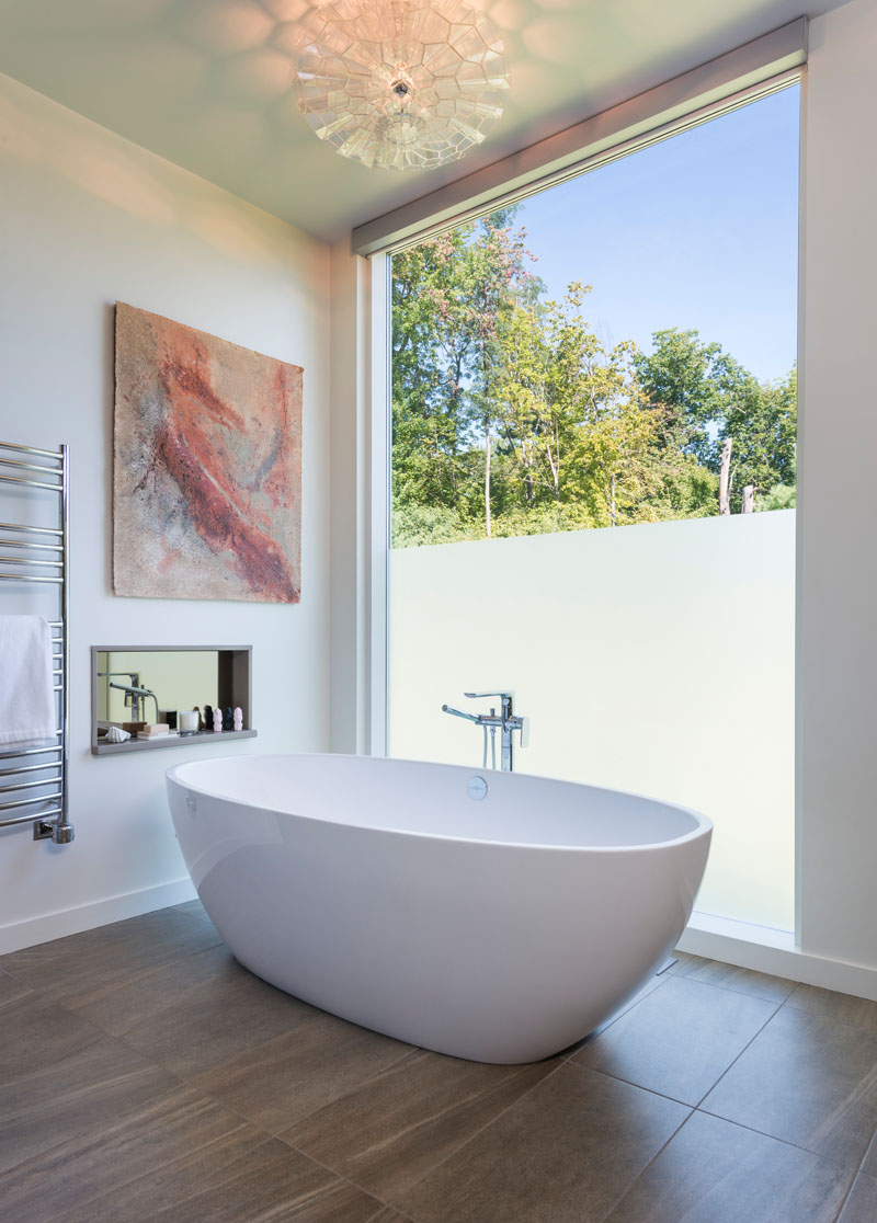 In this modern bathroom, an oval freestanding bathtub sits in front of a partially frosted floor-to-ceiling window.