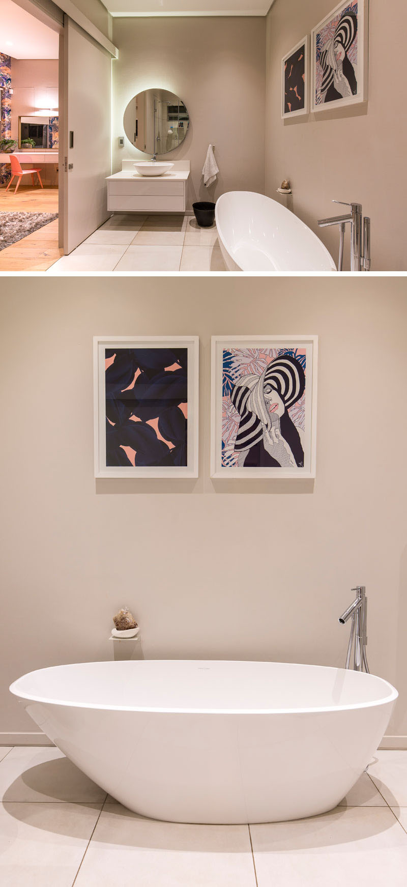 The freestanding bathtub in this modern ensuite bathroom sits below two white framed graphic images that match the bright wallpaper in the bedroom. A round backlit mirror provides extra light in this space and sits above a simple white vanity.