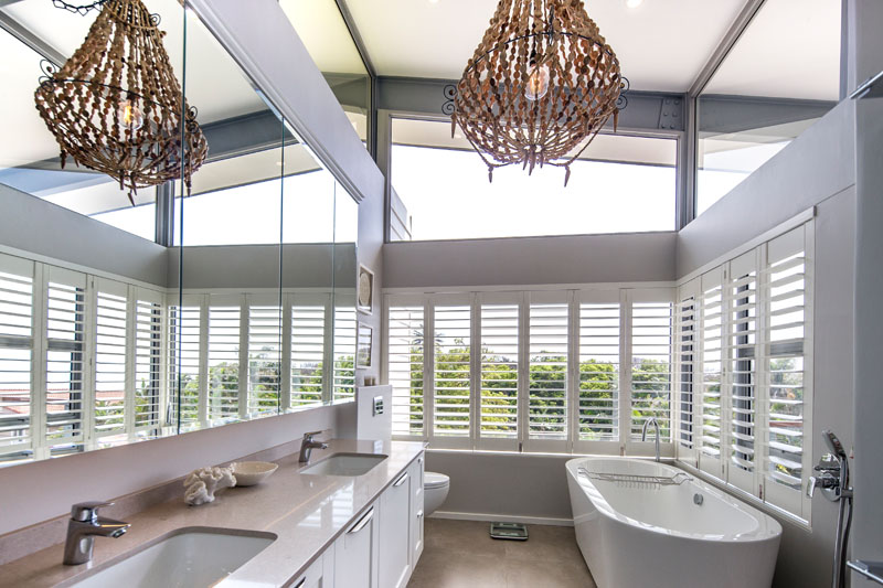 In this modern bathroom a free standing bathtub is situated by windows that are covered by white shutters. Clerestory windows add extra light to this airy washroom.