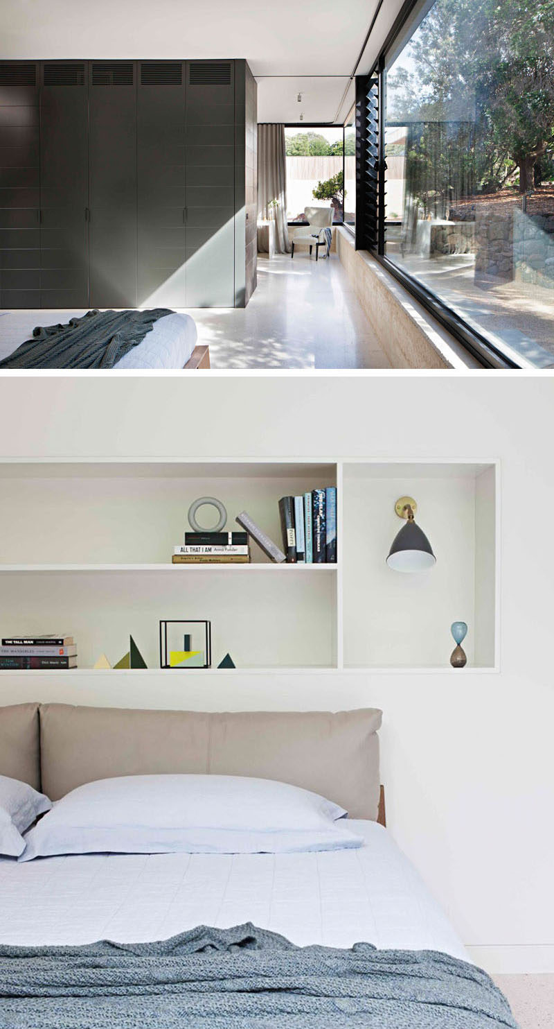 This modern bedroom is tucked around the corner from the study. It looks out to the garden and a wall of dark cabinetry lines the wall. Shelving above the bed provides a place to store favorite books and decorative elements.