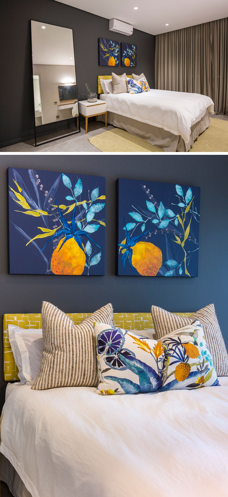 Colorful paintings, bright fabrics on the bed, and the light green headboard stand out against the dark blue accent wall in this modern bedroom. The large mirror beside the bed, reflects the ceiling lights used in this room.