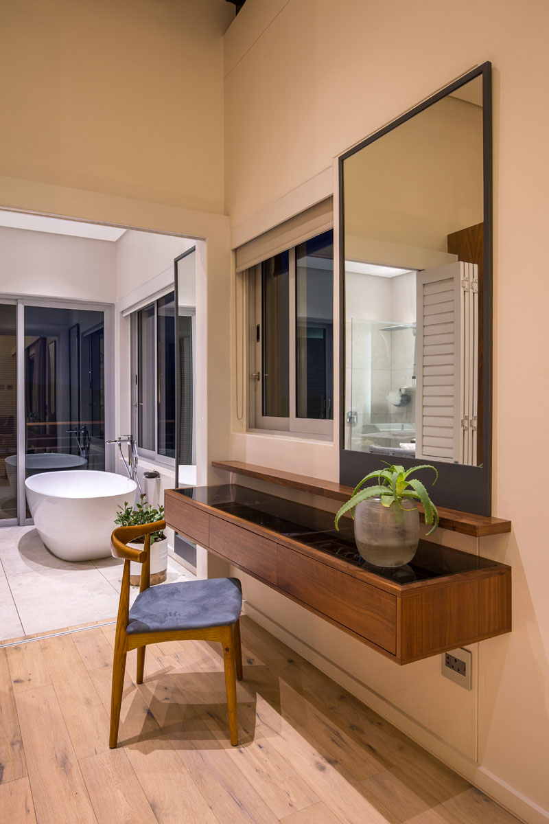 A small space before the walk-in closet and bathroom provides the perfect spot for a modern wood vanity with a large rectangular mirror, and a delicate wood chair.