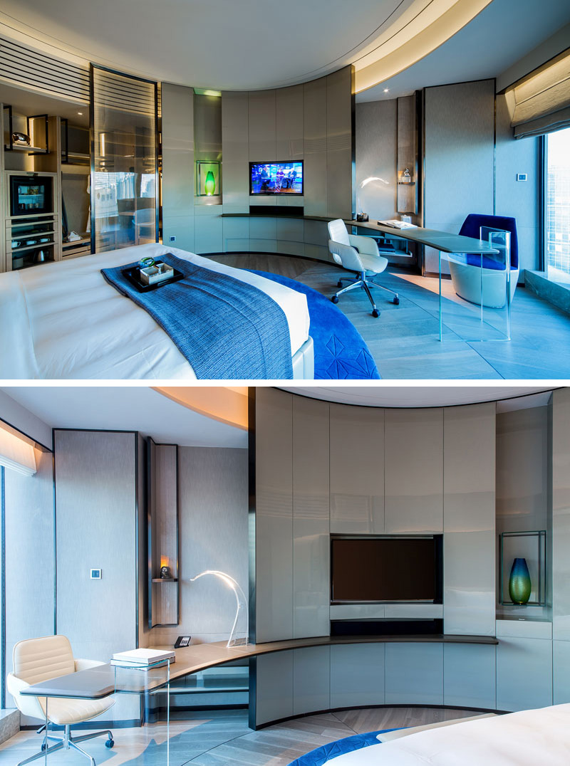 The rooms inside this modern hotel have a simple blue color palette and are minimally decorated. A curved wall with a built-in TV is a main design element, creating the effect of a circular room.