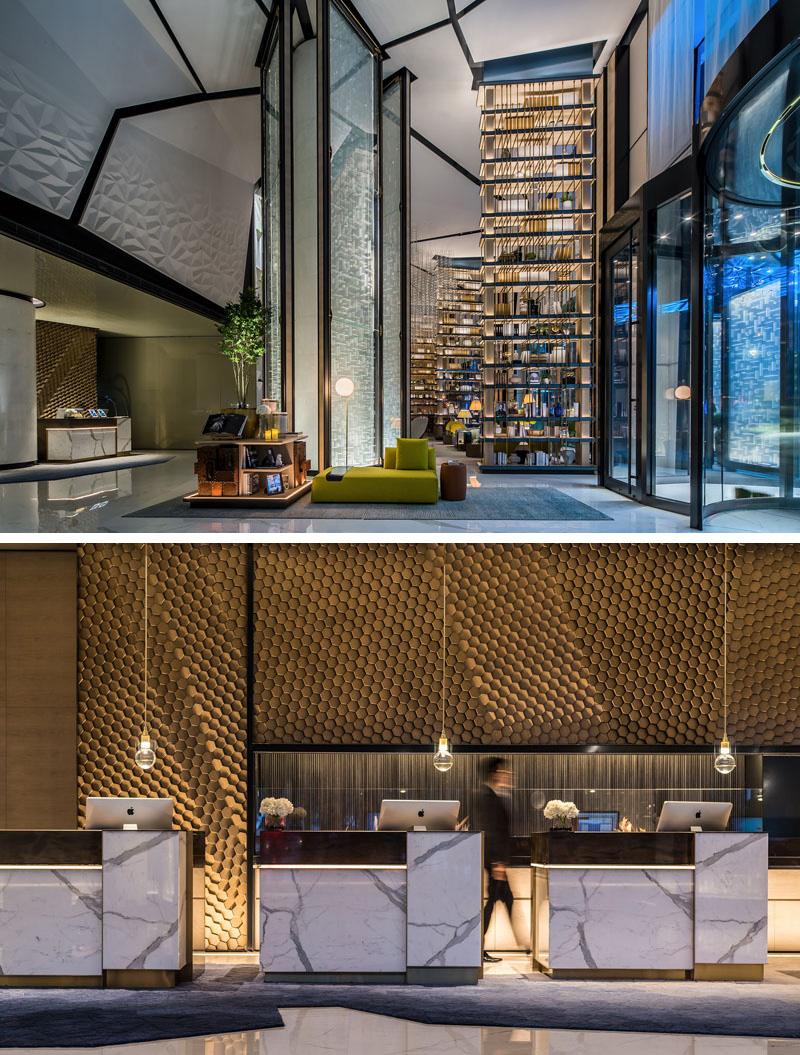 Arriving in this modern hotel lobby, a blend of materials, textures, and geometric patterns can be seen everywhere. The marble and gold front desks sit below individual pendant lights, and in front of a gold textured honeycomb wall that looks like it's moving.