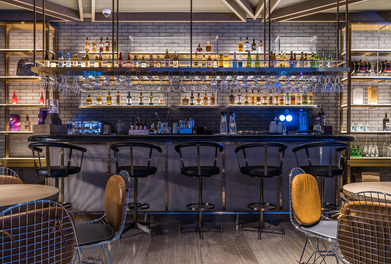 In this modern hotel bar, various metals are used throughout in decor and furniture to create a look that's more casual and laid back.