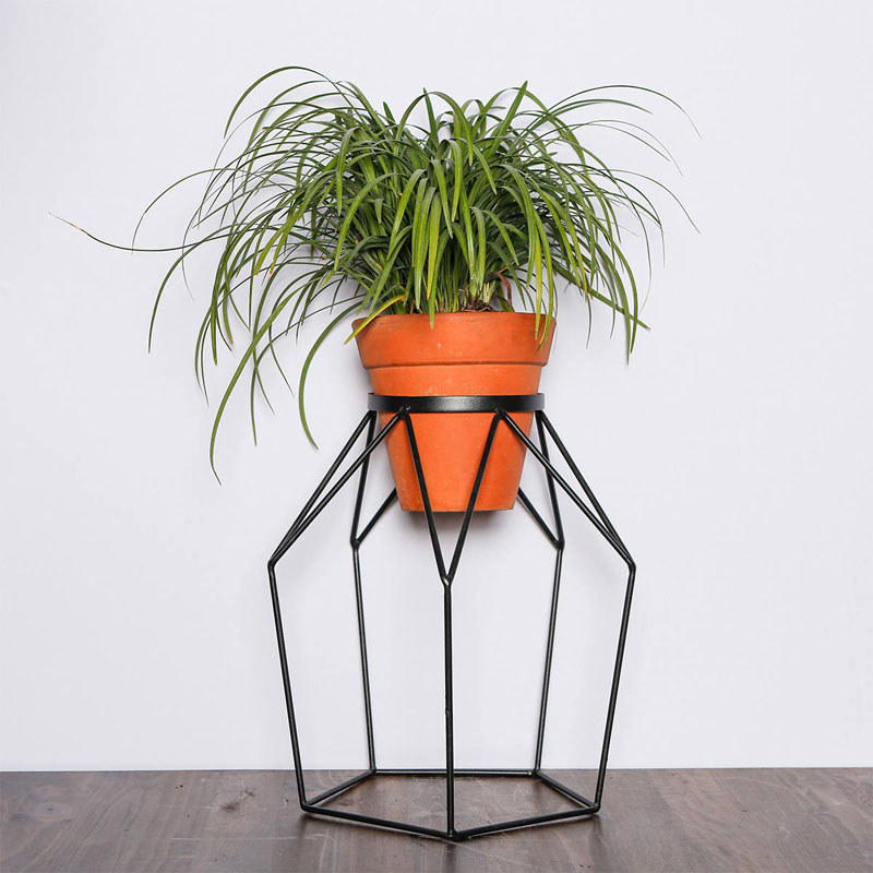With a unique geometric design, this modern black metal plant stand effortlessly holds a potted plant, and decorates a room at the same time.
