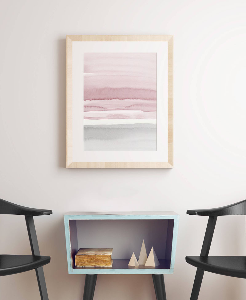 Made with hues greys, whites, and blush pink this watercolor print with a wood frame adds a soft pop of color to the wall.