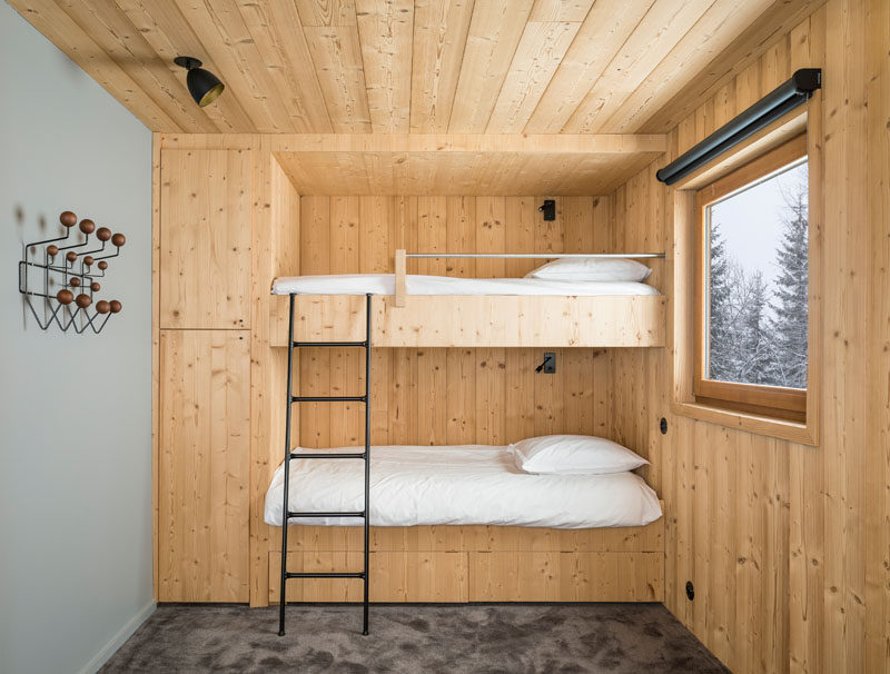 In this rustic modern bedroom, built-in bunk beds with storage cabinets fill one side of the room, while a window adds natural light.