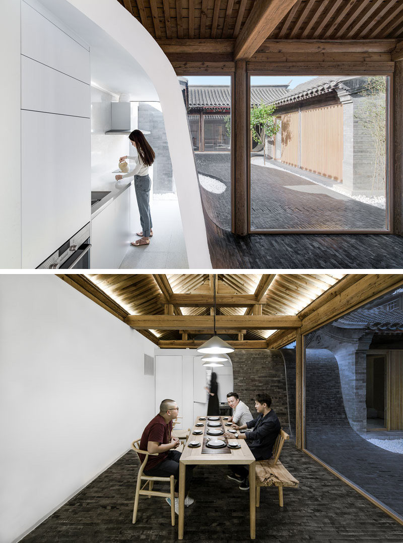 Inside this renovated Chinese building, the small white modern kitchen is tucked behind a curved wall covered in tiles. In the dining area, a long wood table sits below a set of three pendant lights.