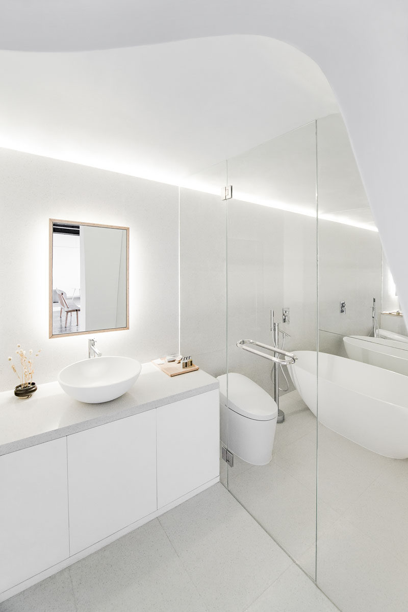 In this modern all white bathroom, there's a curved ceiling element and hidden lighting in the ceiling. A back lit mirror makes this bright room even lighter.