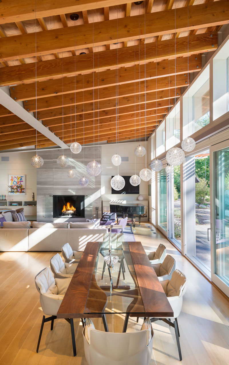 Delicate pendant lights have been used to create an artistic installation above the dining area in this open interior.