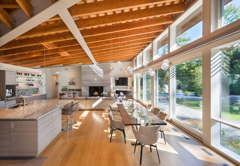 The main living area of this modern house has high ceilings with exposed beams and large 12 foot sliding glass doors that open up to a landscaped yard.