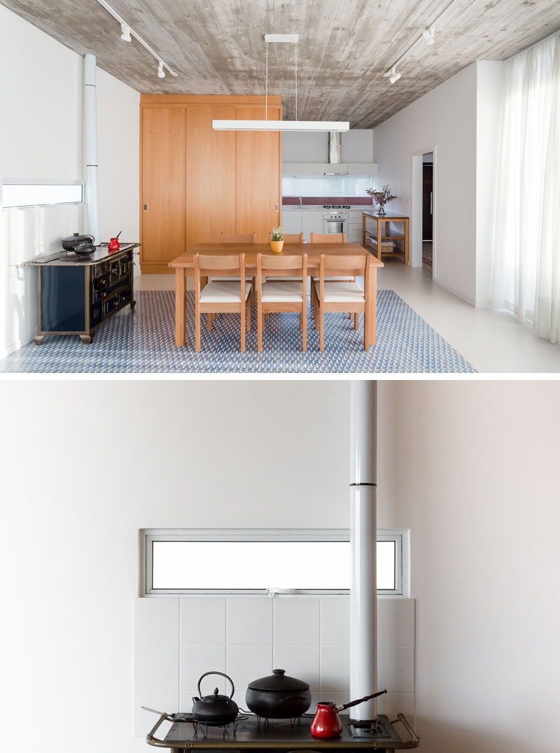 The furniture throughout this modern home was chosen for its practical use and not just decorative, like the wood dining table by a local artisan and the wood fire stove.