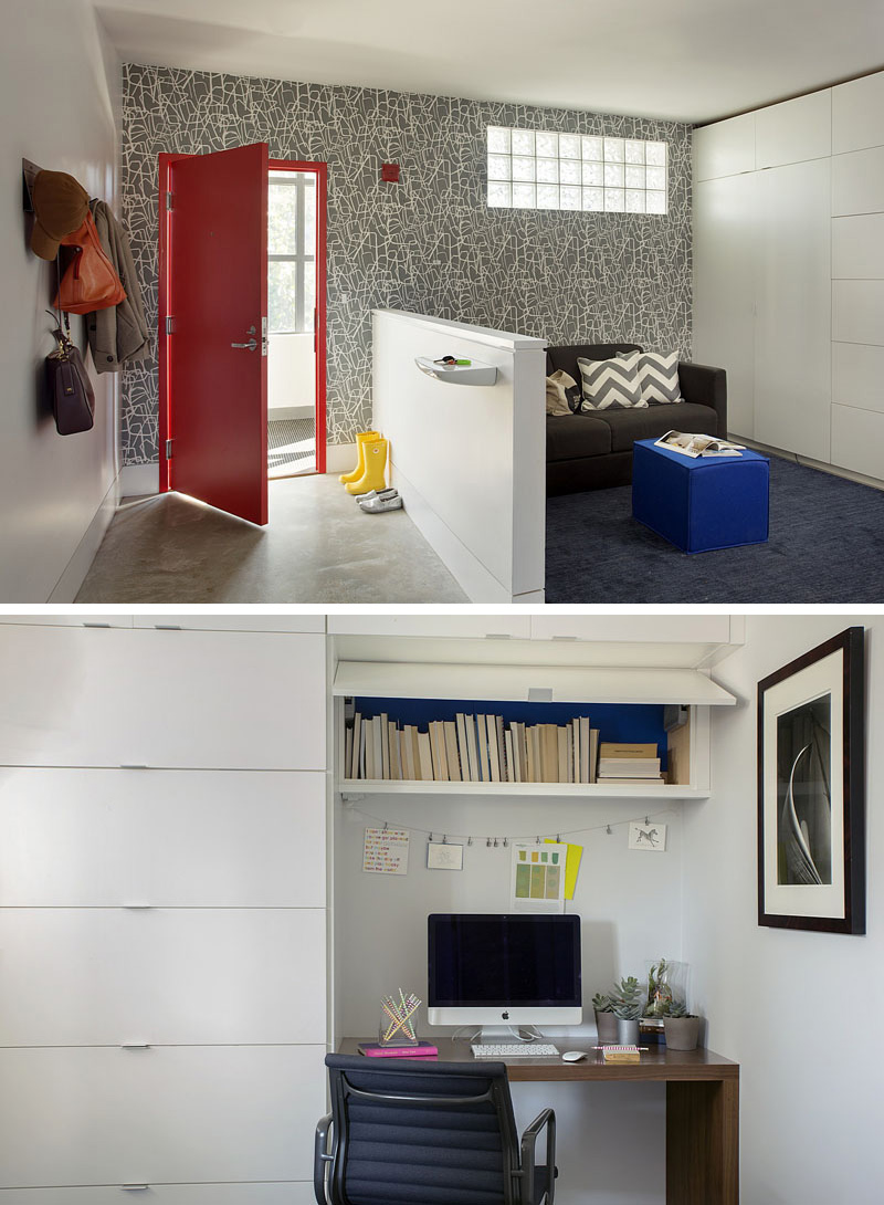 Just inside the front entrance of this modern loft, is a small sitting room with a wall full of floor-to-ceiling white cabinets. This area can be used as a home office (there's a small desk built into the cabinets) or as a sleeping area for guests. A red door and graphic wall paper give this space a bright and fun feeling.