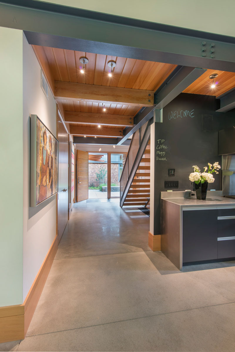 Light concrete floors, plaster walls, wood ceilings and steel beams make up the material palette of this modern house.