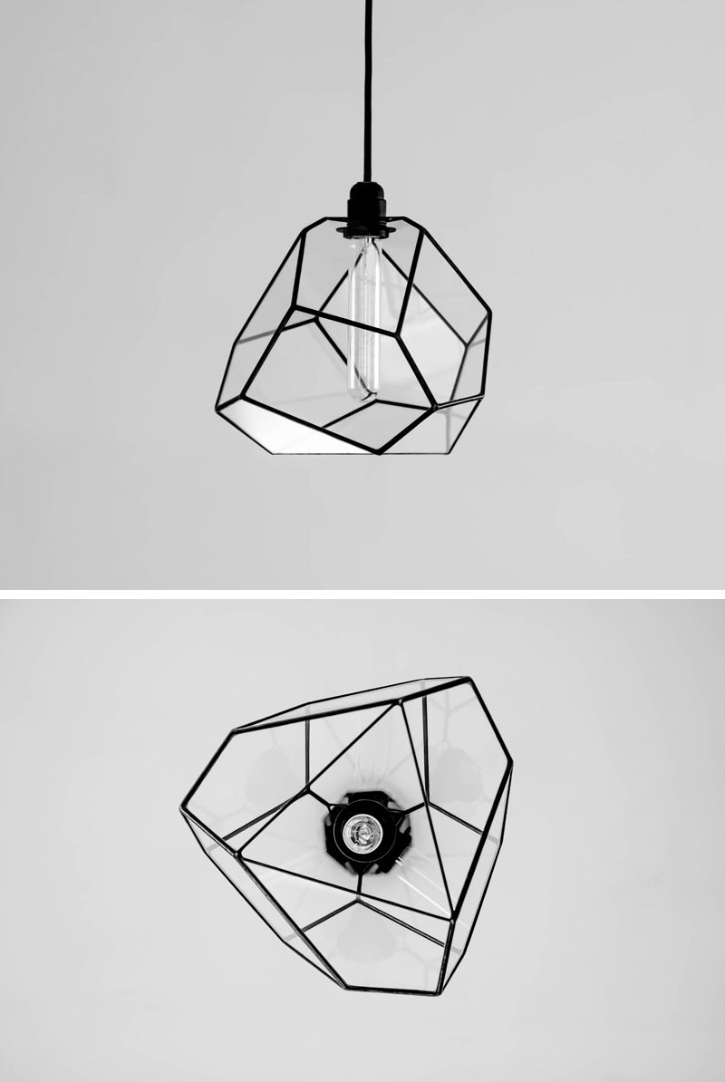 A modern glass pendant light with a geometric shape and black accents.