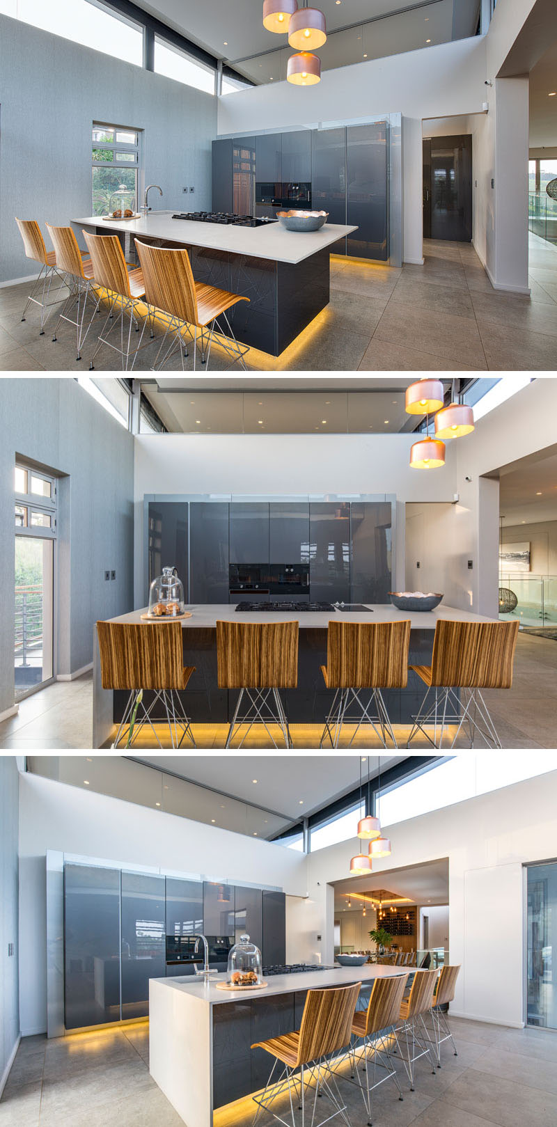 This modern kitchen has hidden lighting below the grey island and wall of cabinets make it appear as if they are floating. The glossy finish on the surfaces reflect the light making the room feel bright and open.