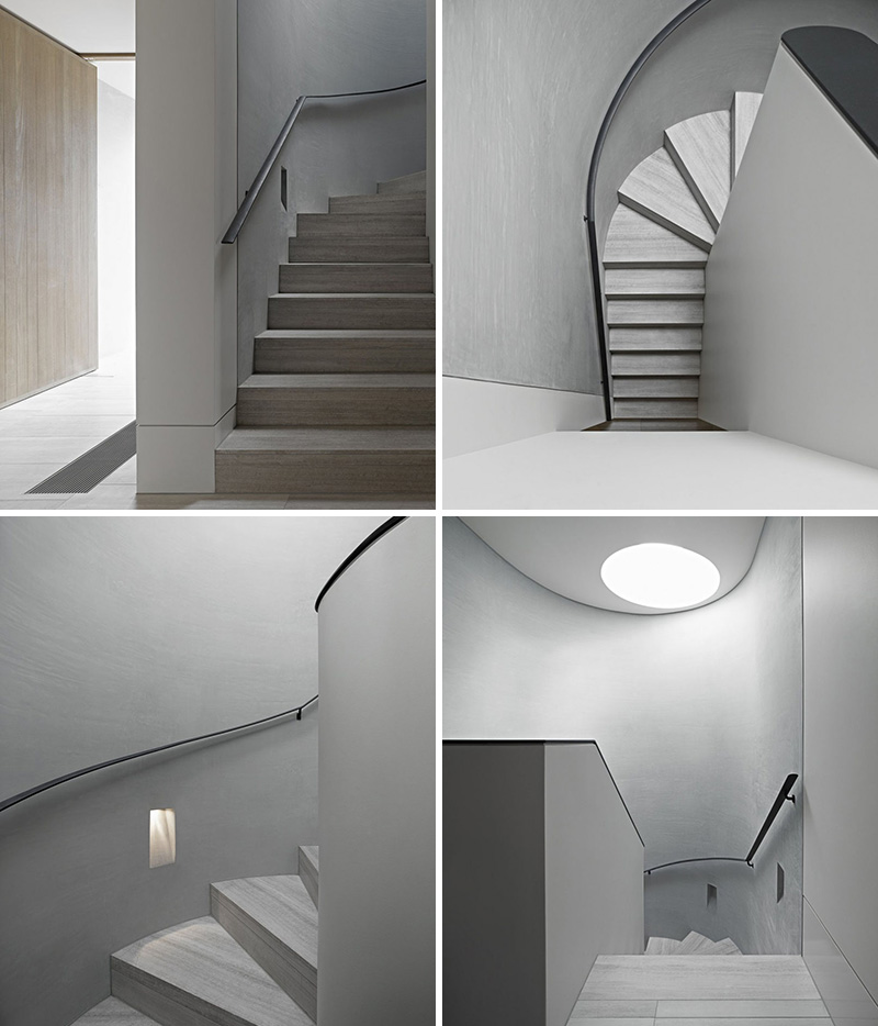 These modern curved grey stairs lead to the other levels of the home, while a circular skylight provides natural light to the stairwell.