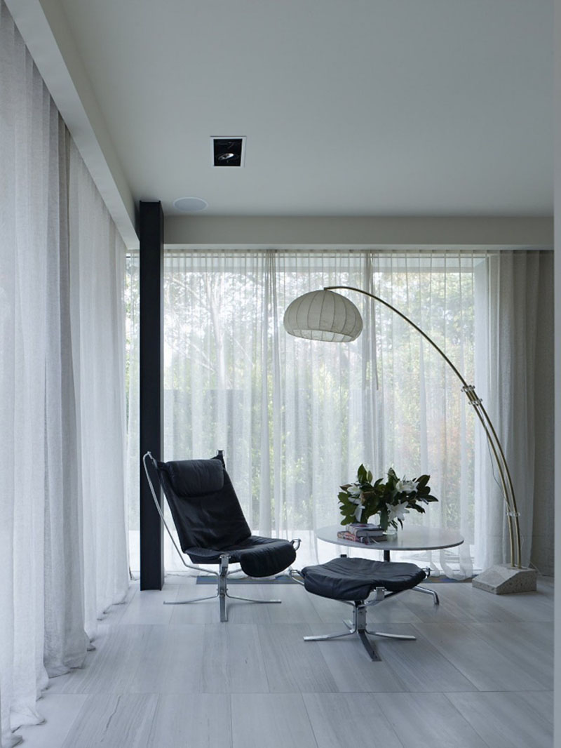 Stepping inside this modern home, a large floor lamp with a white shade provides light above a black upholstered leather chair and a small table.