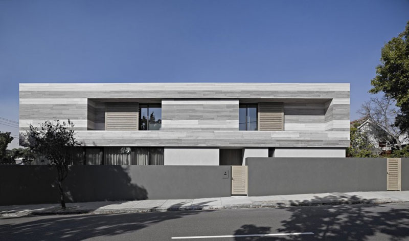 Designed by b.e.architecture, this modern grey house in Melbourne, Australia was made using a limited color palette. Natural and aged materials have been used to create the rectangular home.