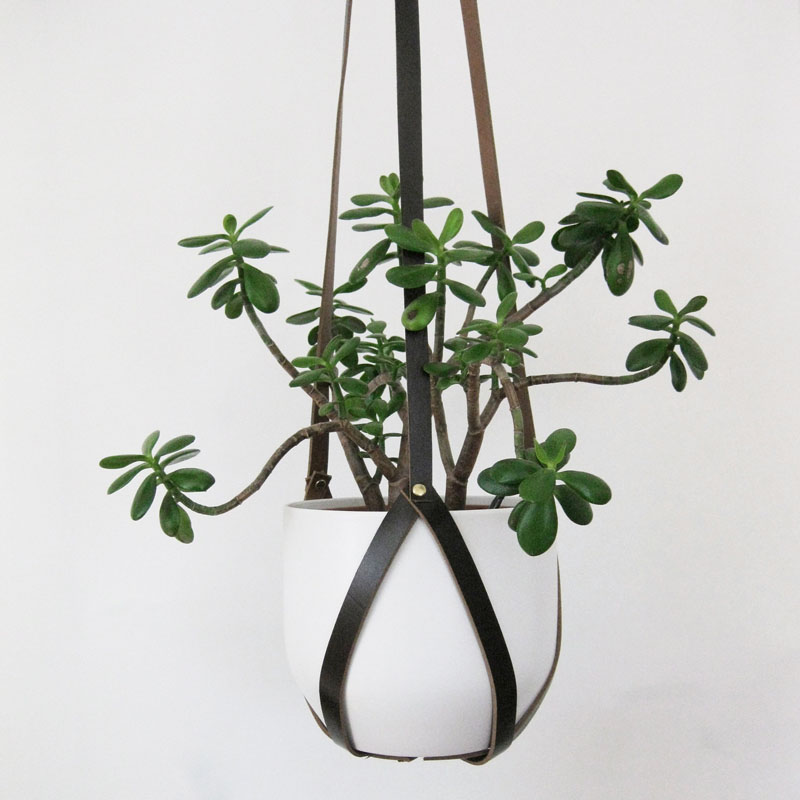 Made from recycled tan leather, this modern hanging planter is 3.5 feet (1.1m) long and has brass rivets that can be adjusted to accommodate for the size of a pot.  #HangingPlanter #ModernPlanter #HomeDecor #Garden #Plants