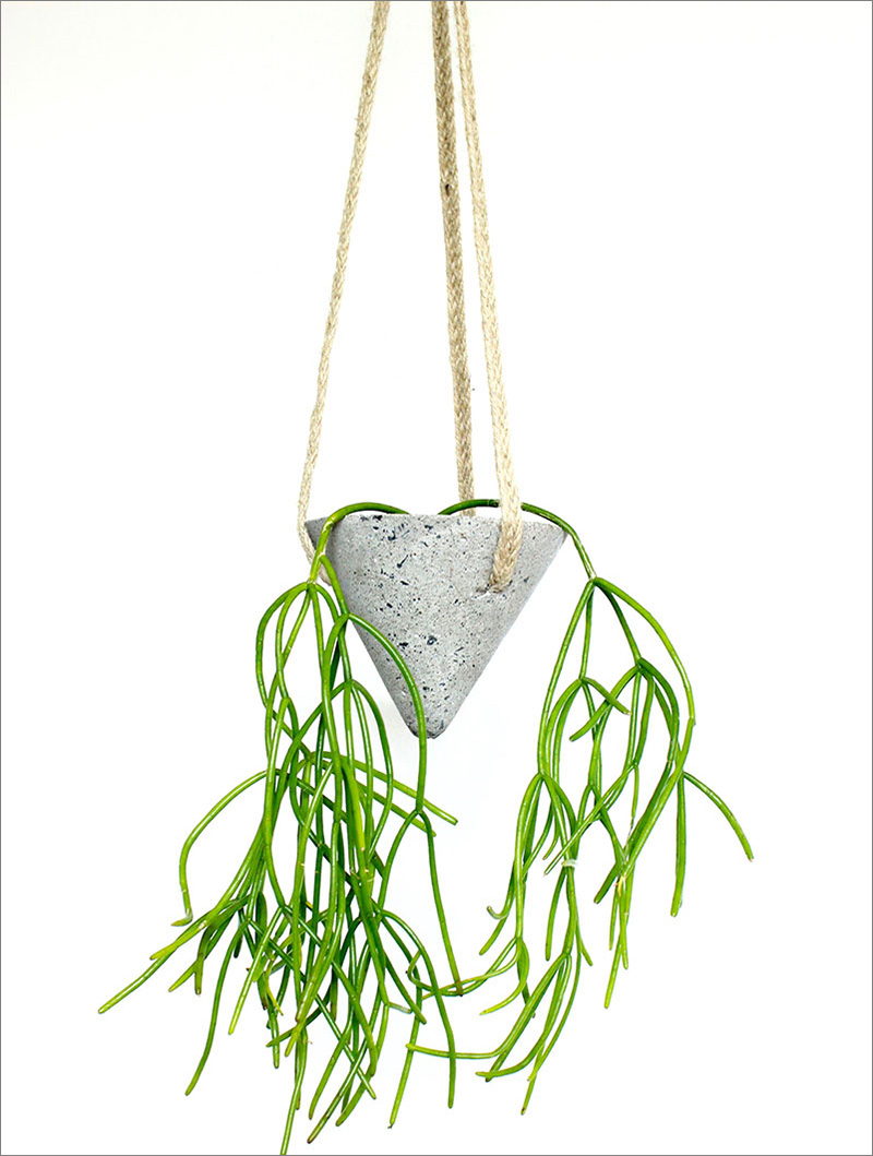 Triangular in shape, this modern concThis cone-shaped concrete planter is hung from rope, and is ideal for when you want to add an industrial touch to any interior.rete planter is hung from rope, perfect for both an industrious work space, and at home.