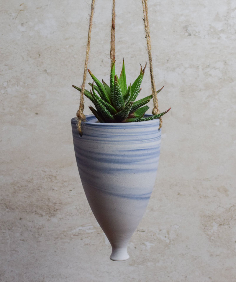 This blue and white ceramic hanging planter has a elongated shape and a marble effect.
