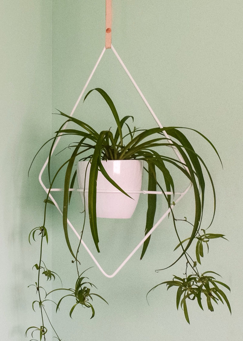 This white geometric planter is made front steel and hangs from a simple leather strap, while the shape of the planter frames the plant as an art piece.  #HangingPlanter #ModernPlanter #HomeDecor #Garden #Plants