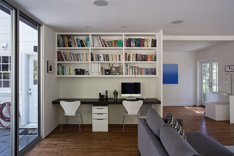 A black desk built-in below the white shelves makes this small space a functional home office for two.