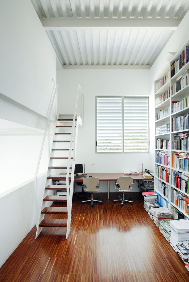 Almost entirely white, this office for two has a near floor-to-ceiling bookcase, and a set of stairs that lead to another room. The wood desk below the white framed window, matches the floor and stairs.