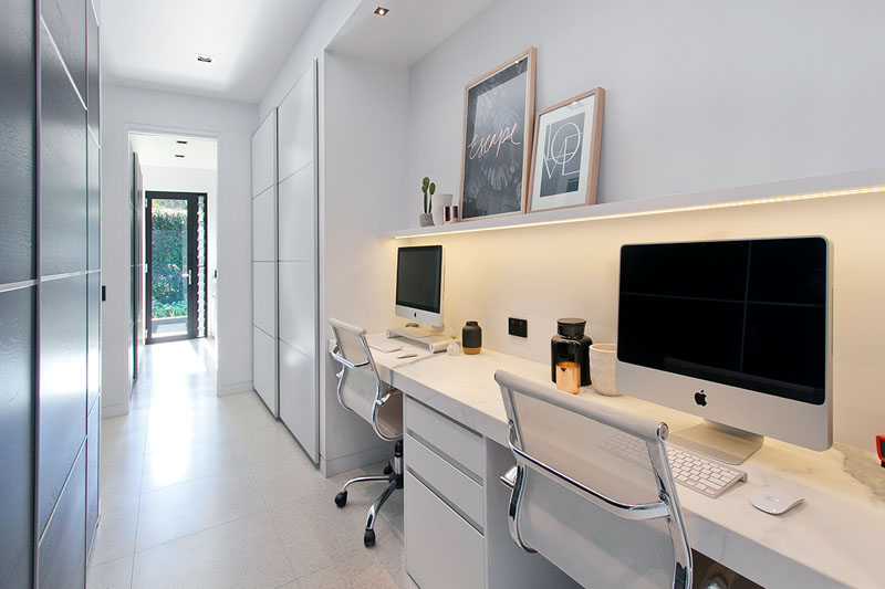 with enough room for two this large desk sits below a small floating shelf with hidden lighting while the long white hallway provides the perfect space - Modern Home Office For Two