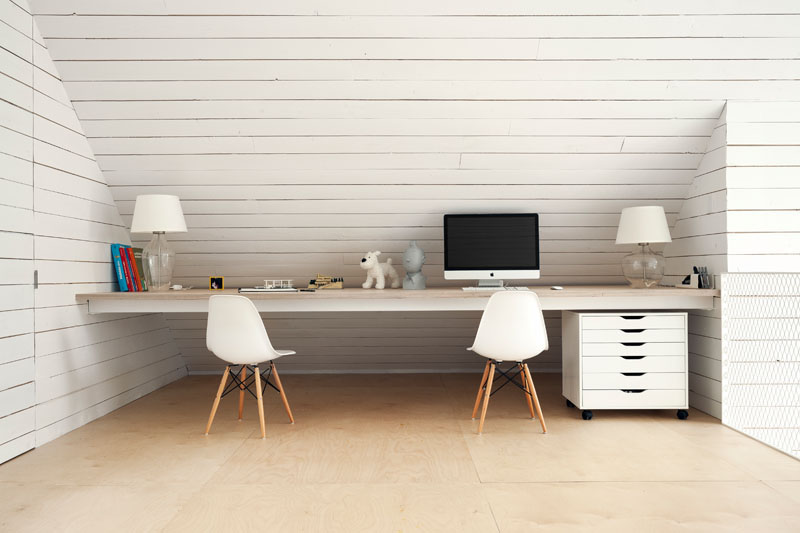 In a room almost entirely of white, this shared desk is creatively tucked in below the roof line creating usable space for this home office.