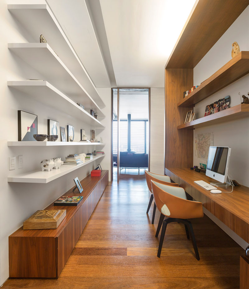 In this home office built for two, wood shelving and long desk are on one side, while floating white shelves for books and decorative displays sit on the opposite wall.