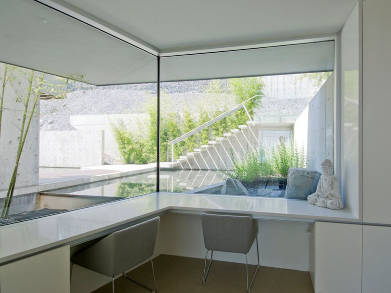 Corner desk space has been built-in below the large wrap around windows of this minimalist home office for two. The white and grey used in this room match the home decor throughout the house.