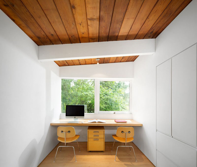 this bright white minimalist home office has a wood ceiling and floor while a floating desk has enough room for two