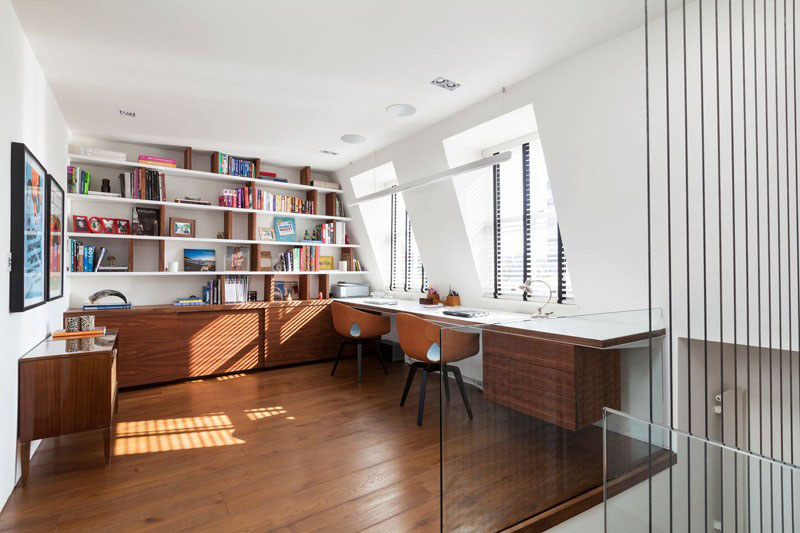 At the top of a flight of stairs, this home office has built-in shelves and cabinets providing excellent storage. The floating desk provides a shared work area and faces two individual windows that look outside.