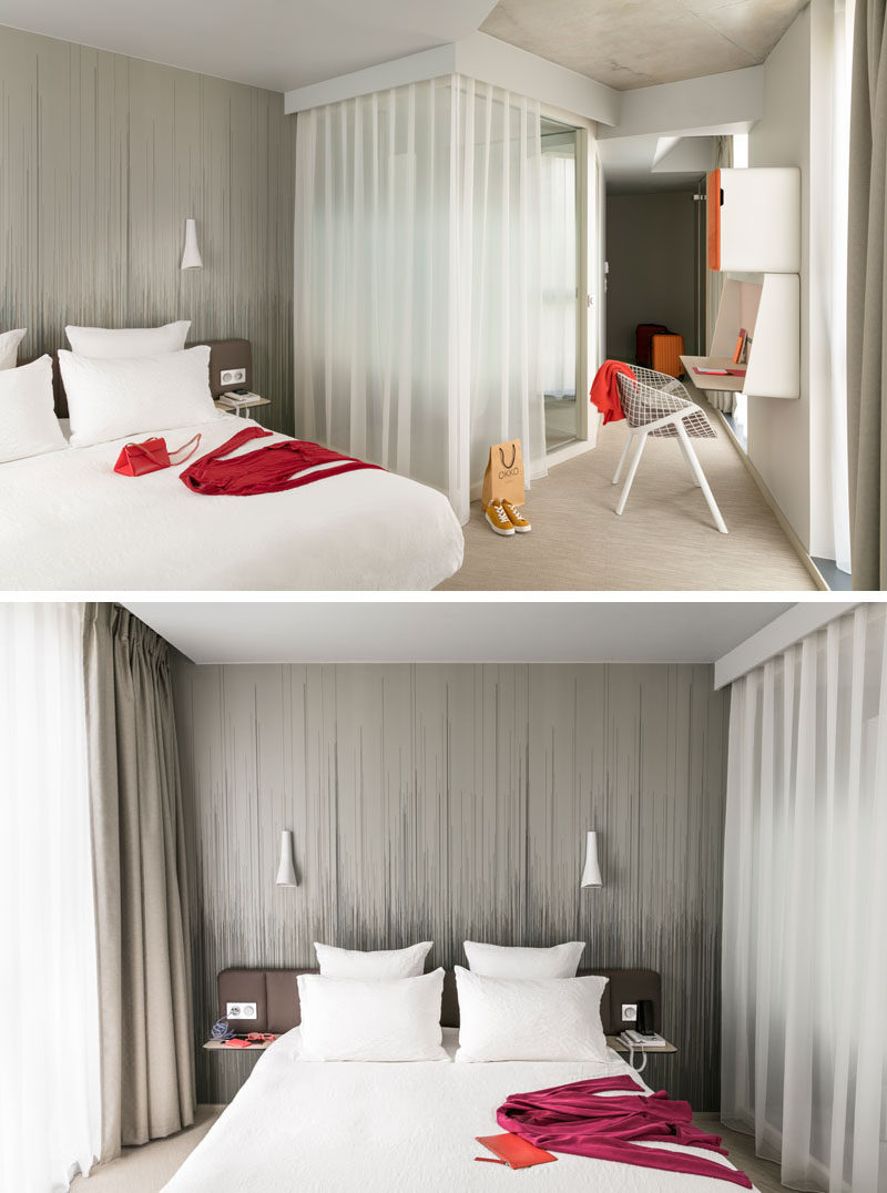 In this modern hotel room, a simple artistic wallpaper creates an accent wall behind the bed and adds to the neutral and sophisticated color palette of the room.